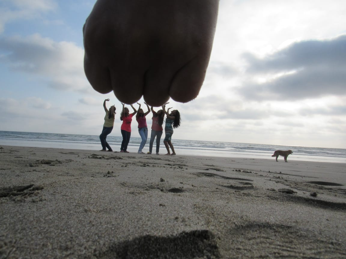 giant hand on beach five girls problem solving