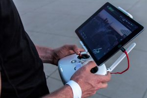 man holding tablet to control drone.